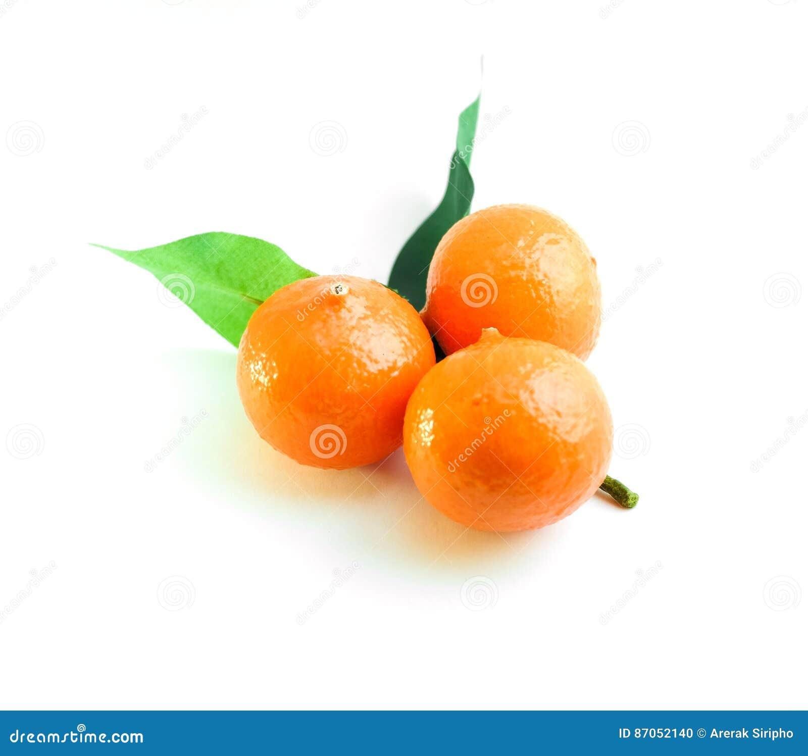 Three oranges and green leaf