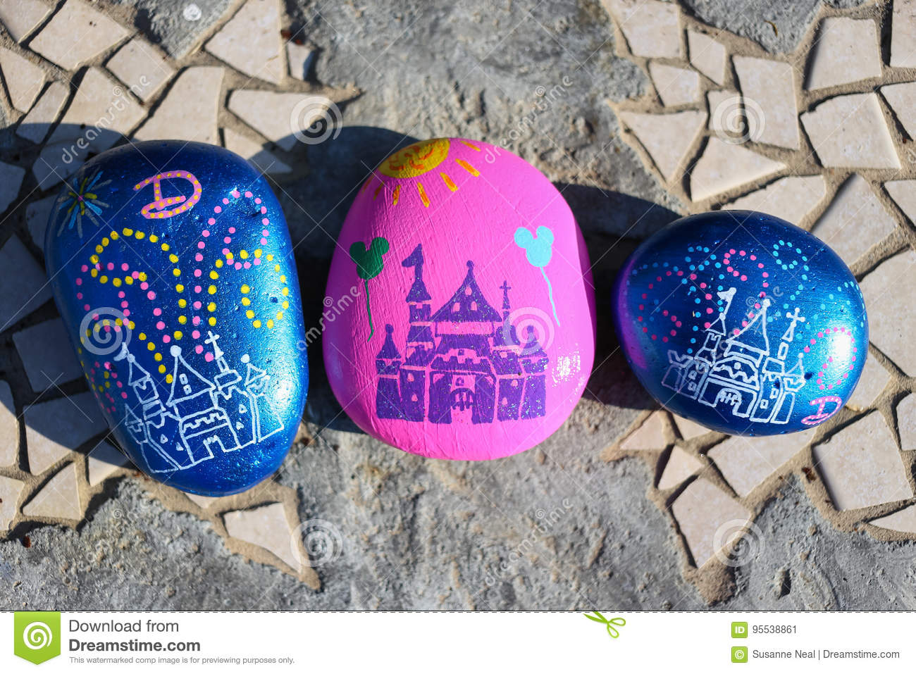 Disneyland stock photos royalty free stock images three painted rocks resembling the castle at disneyland three painted rocks on a garden bench freerunsca Choice Image