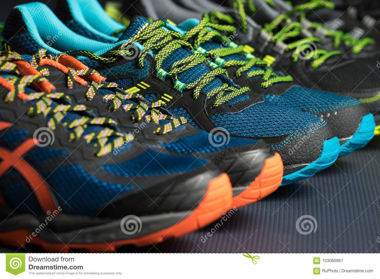 Three pairs of exercise trainers / running shoes on a gym floor