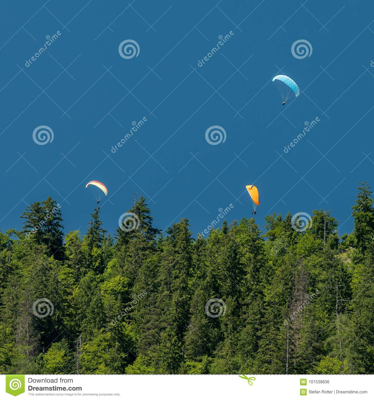 Three paragliders in the mountains blue sky