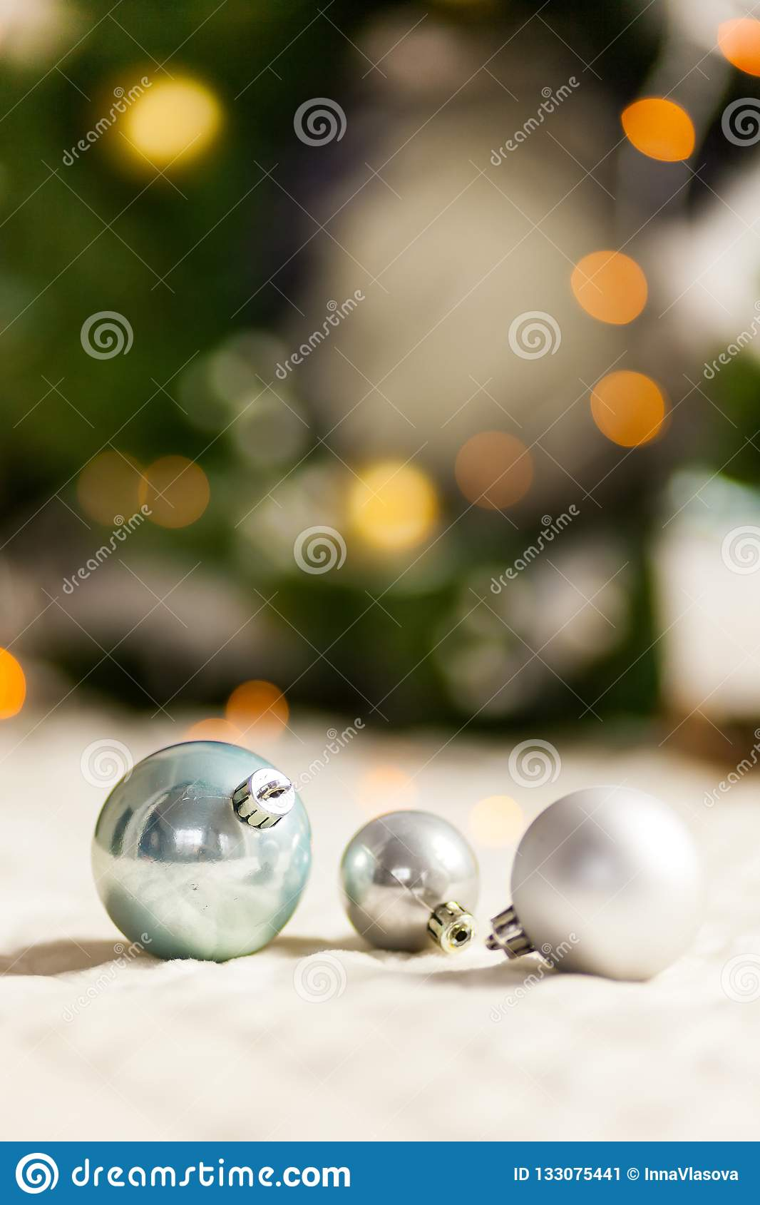 Three Pearl Christmas balls with colorful bokeh