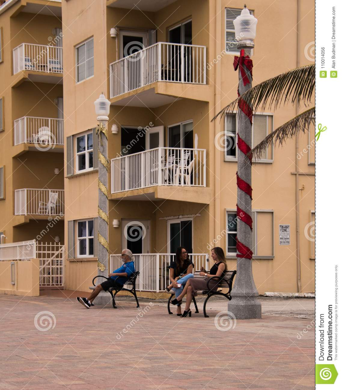 Three people on benches in Hollywood, Florida