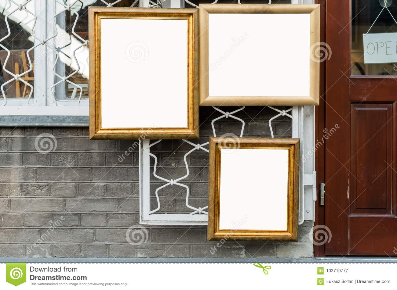 Three picture wooden frames on the wall outside Art Gallery, B