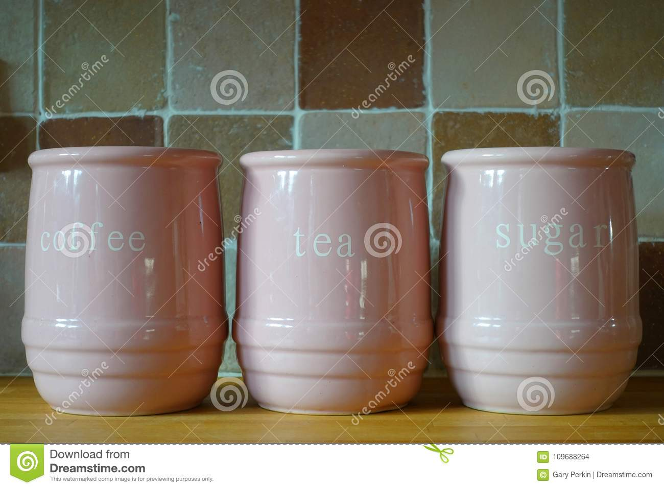 Three pink jugs on a wooden kitchen work surface, with the words