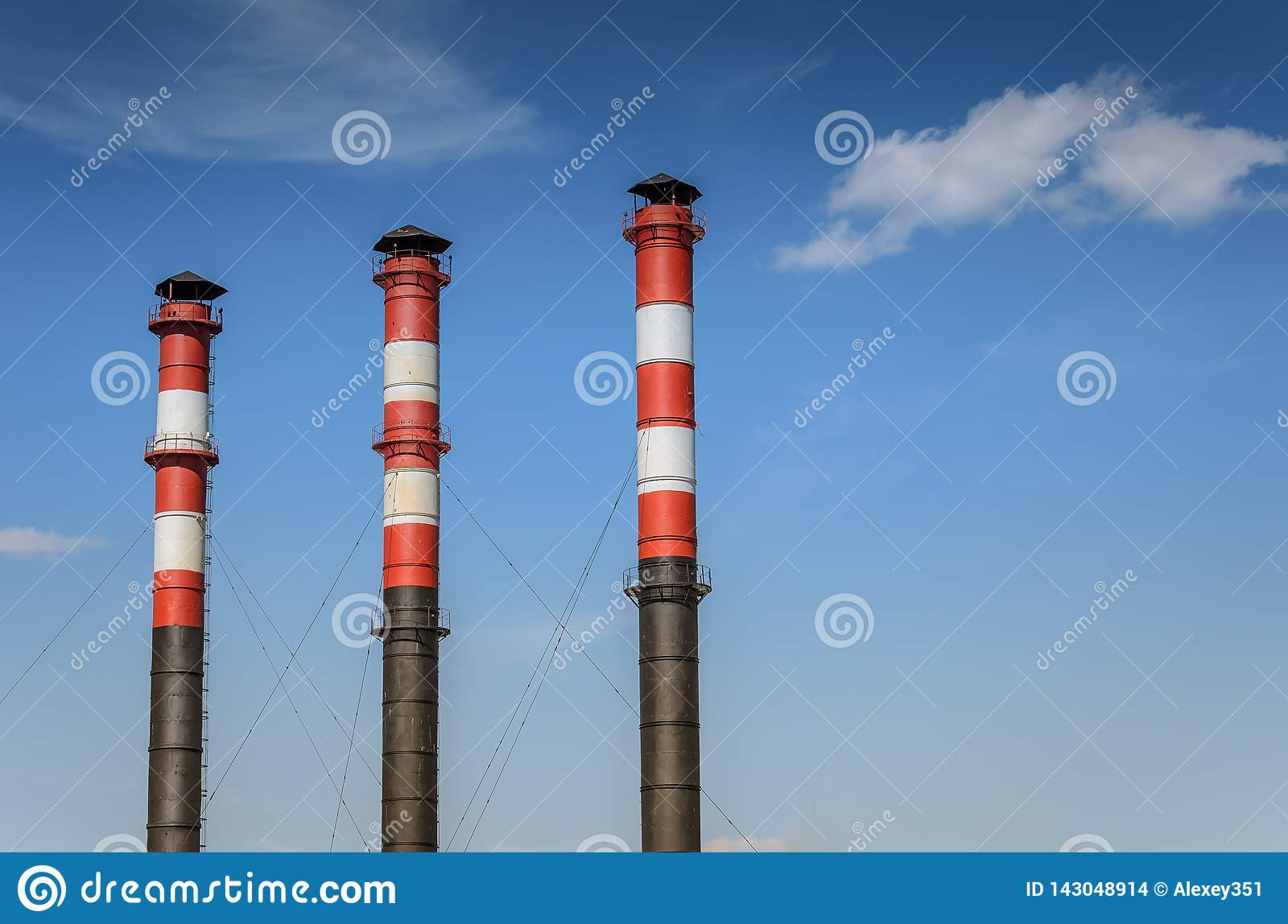 Three pipes of plant against background of blue sky/pipes of the plant against the background of the sky