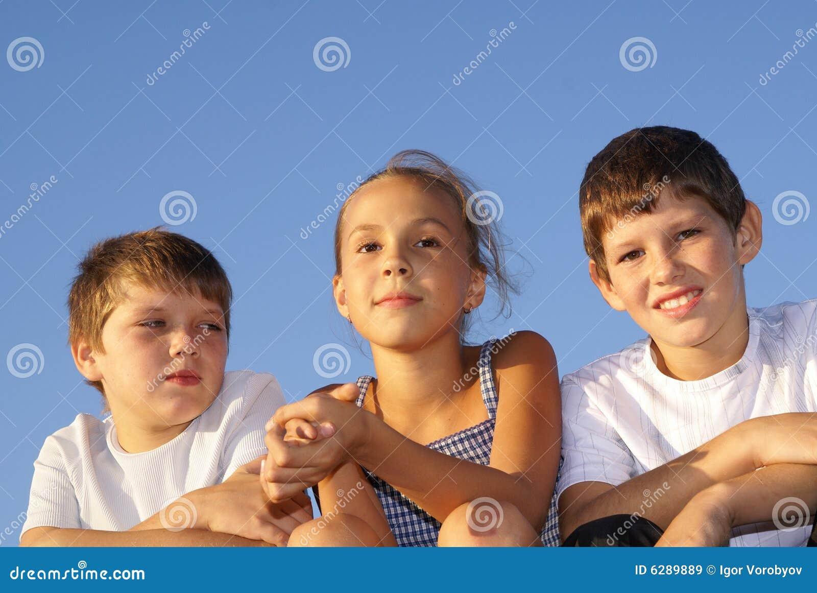 Three preteen friends enjoying summer outdoors on blue sky background.