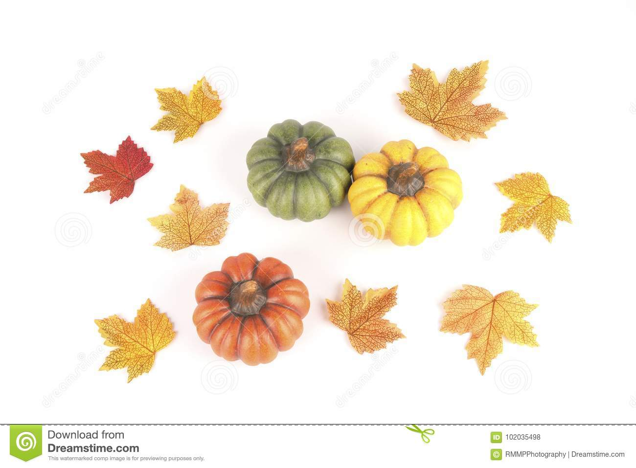 Three pumpkins made of clay between colorful leaves