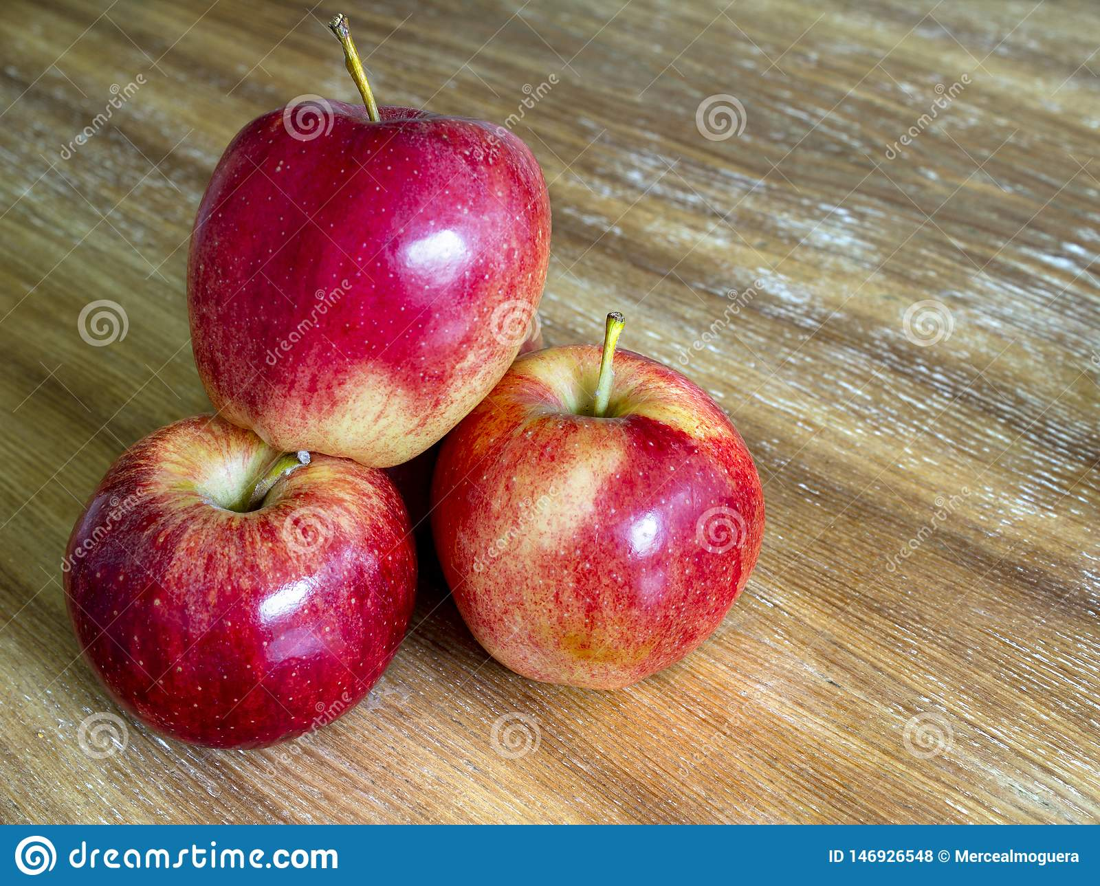 Three red apples isolated on wooden background