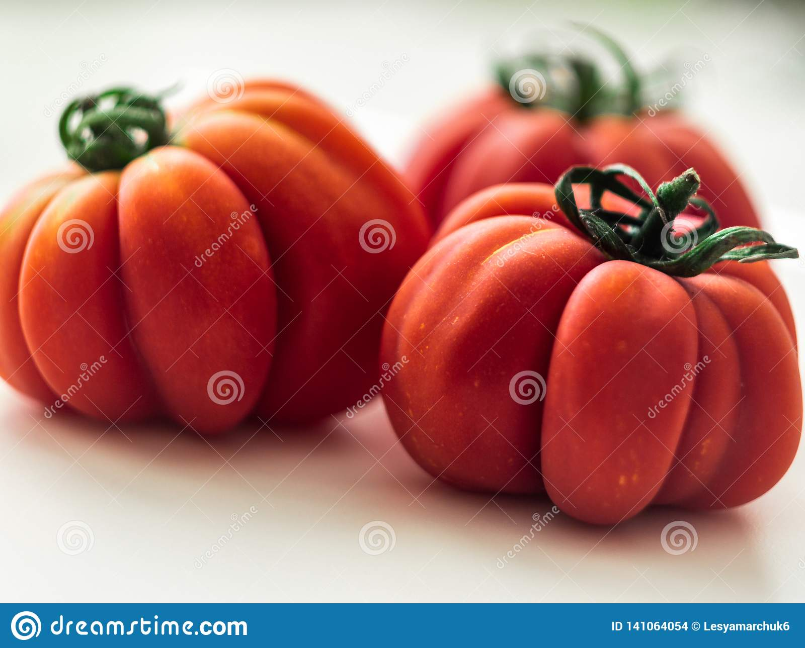 Three red beefsteak tomatoes.