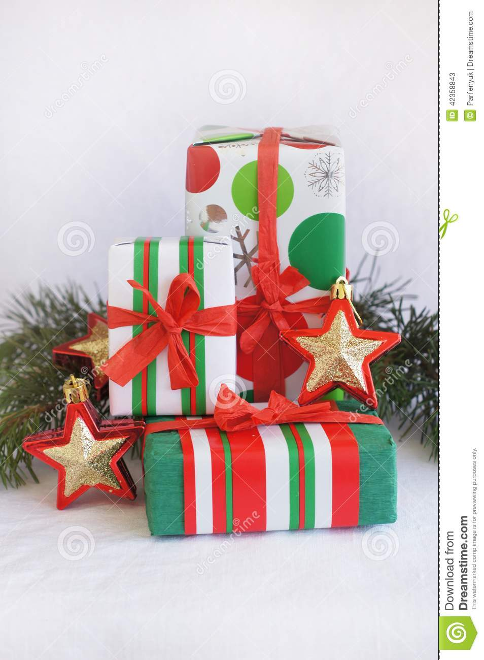 Three red green white christmas gifts with gol stock