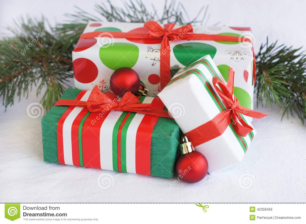 Three red green white christmas gifts with orn stock