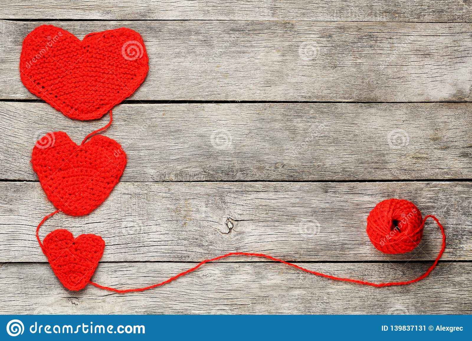 Three red knitted hearts on a gray wooden background, symbolizing love and family. Family relationship, bonds