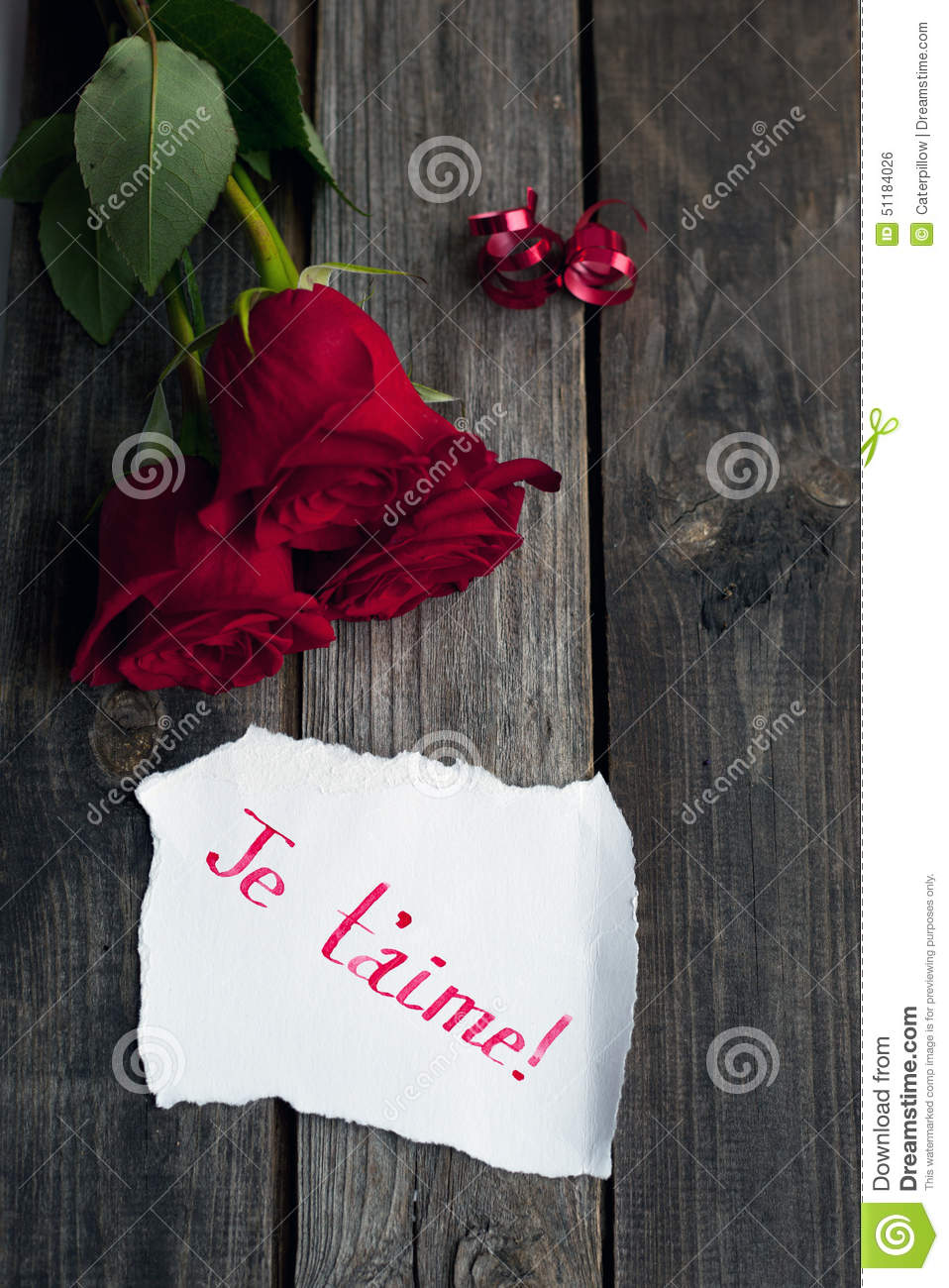 Three Red Roses On Rustic Table With Handwritten Words Je T Aime