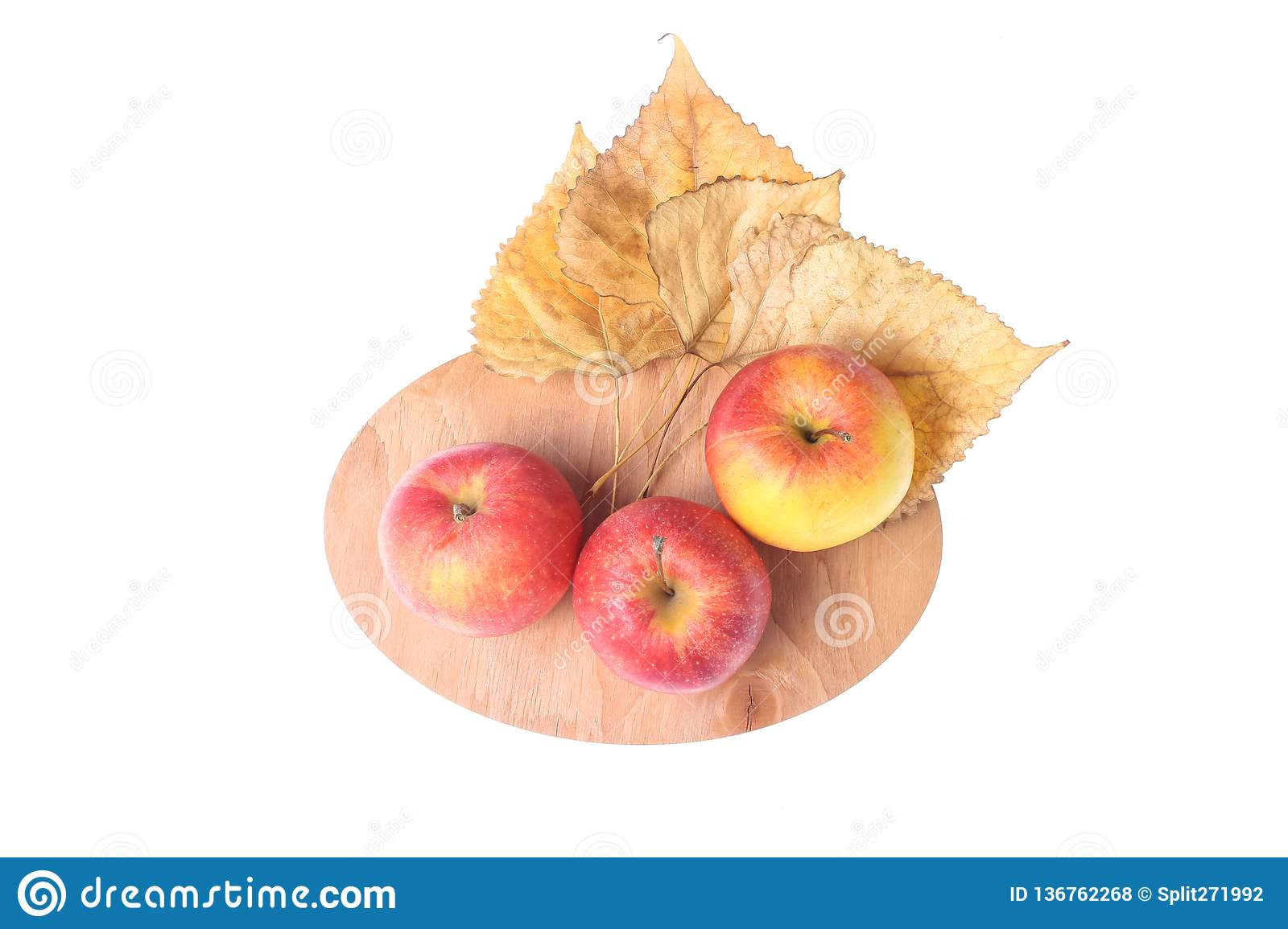 Three ripe apples, fallen leaves