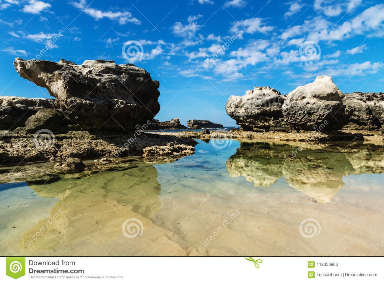 Three rock formations with reflections in the sea at Peterborough beach, Victoria, Australia