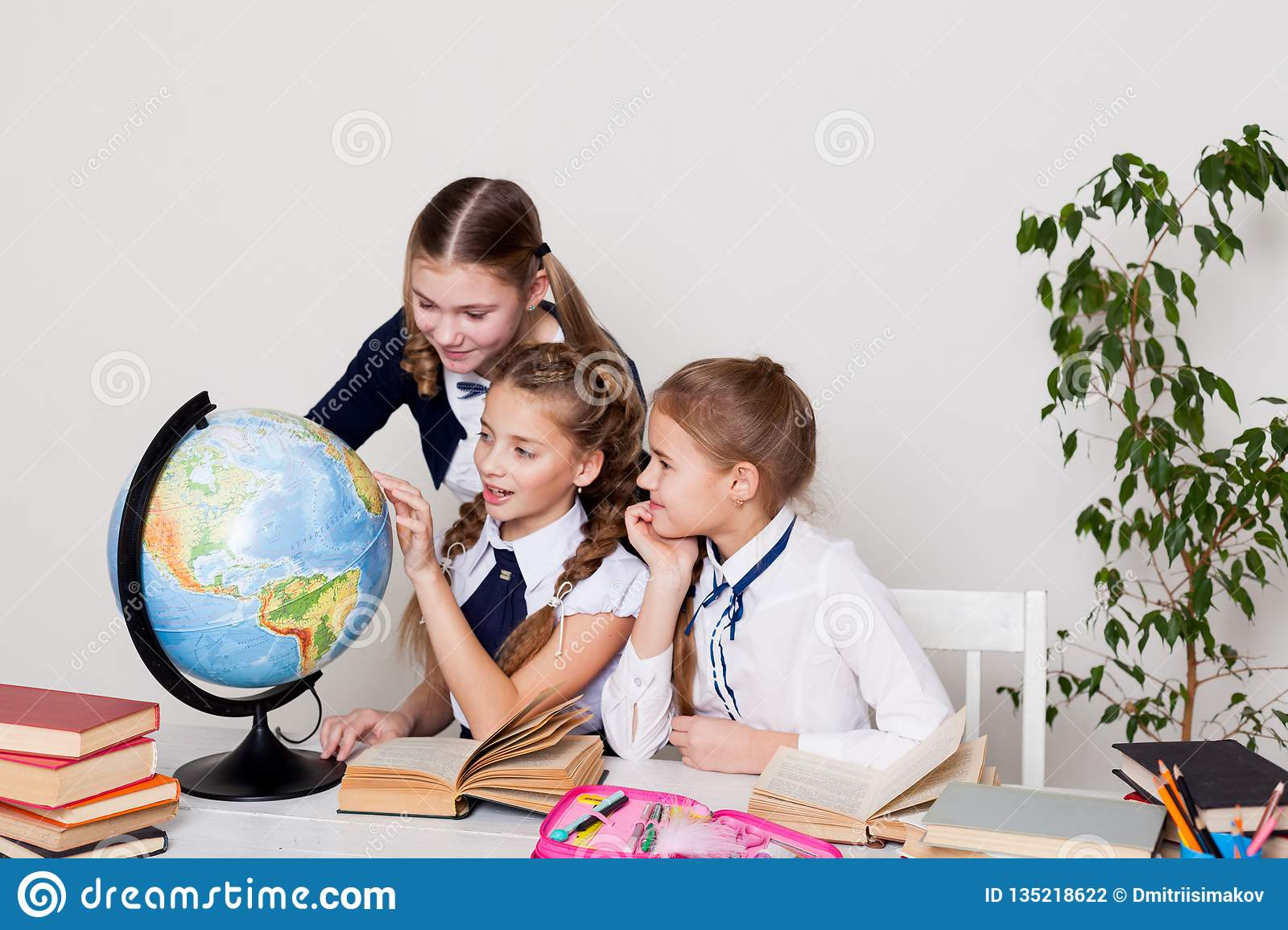 Three schoolgirls girls learn world geography lesson on the map