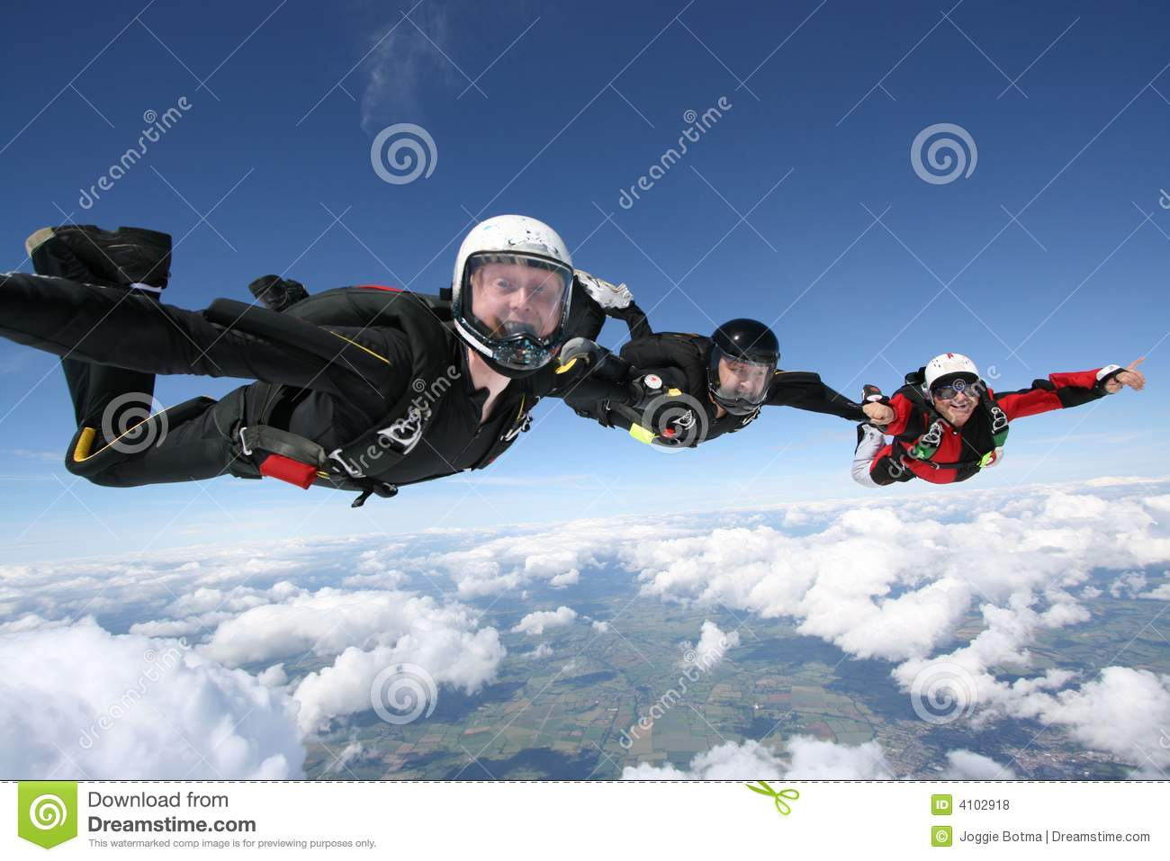 Three skydivers form a line