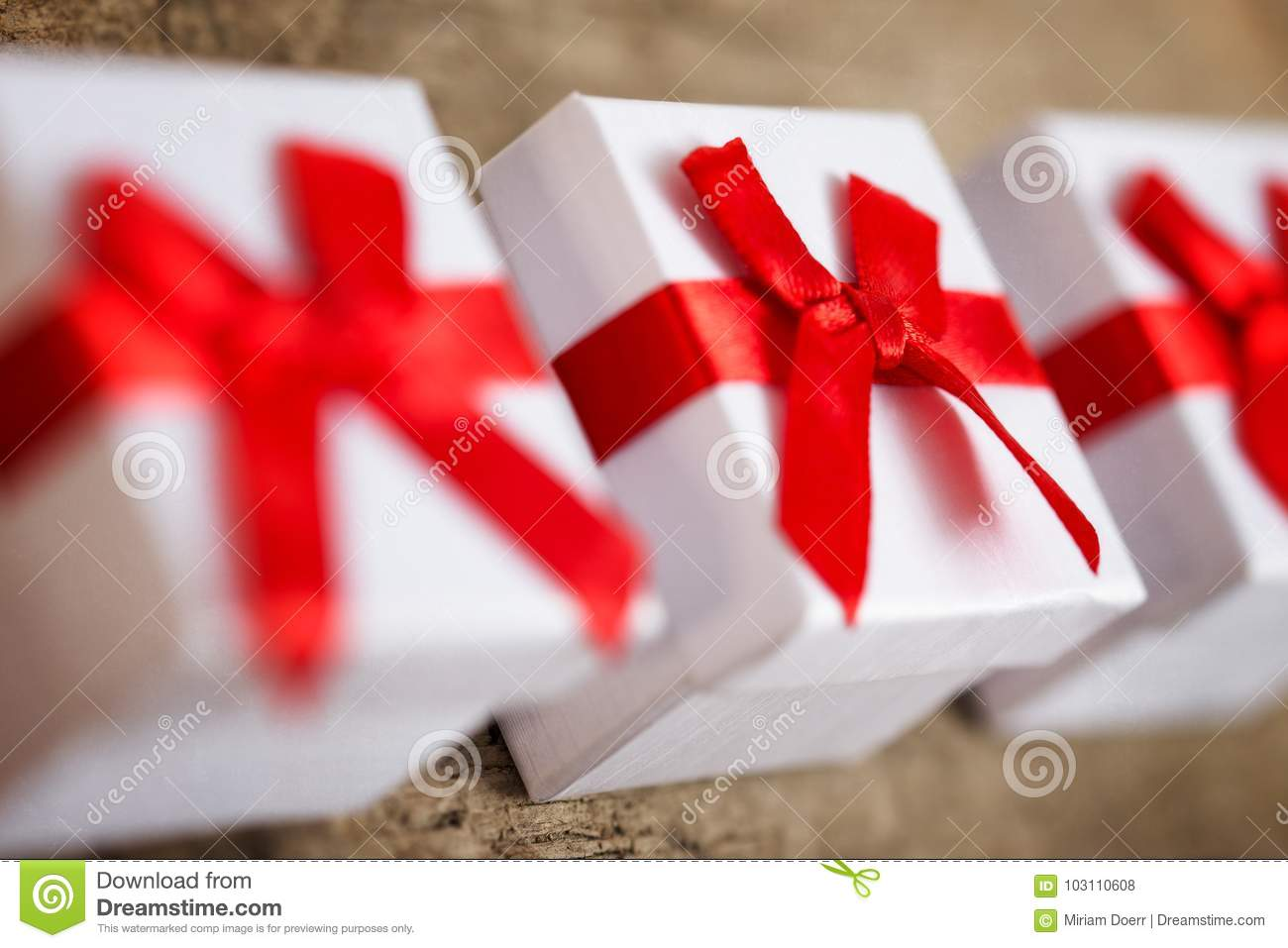 Three Small Gift Boxes For Presents On Wooden Table Stock Photo