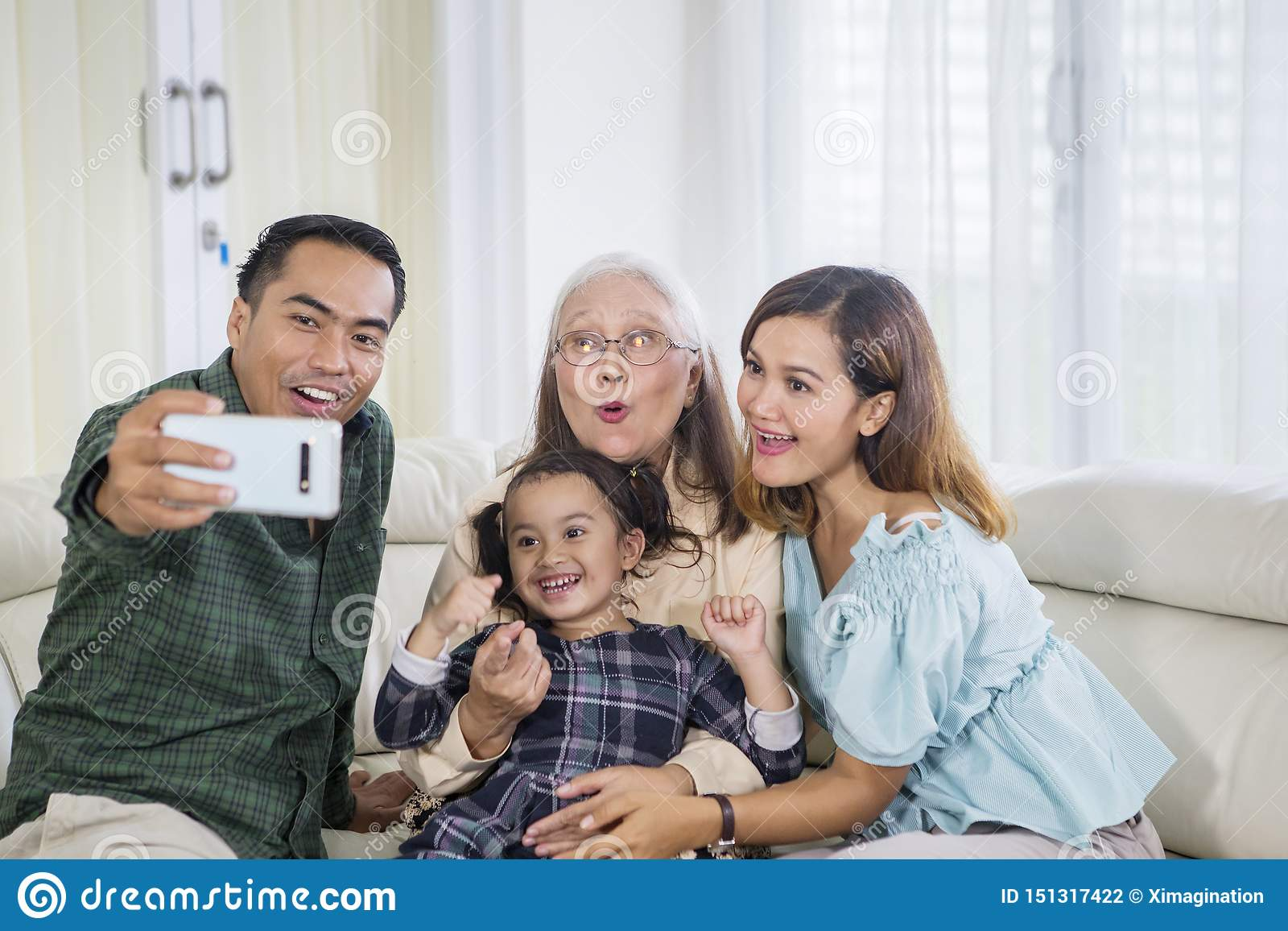 Three smiling generation family takes selfie at home