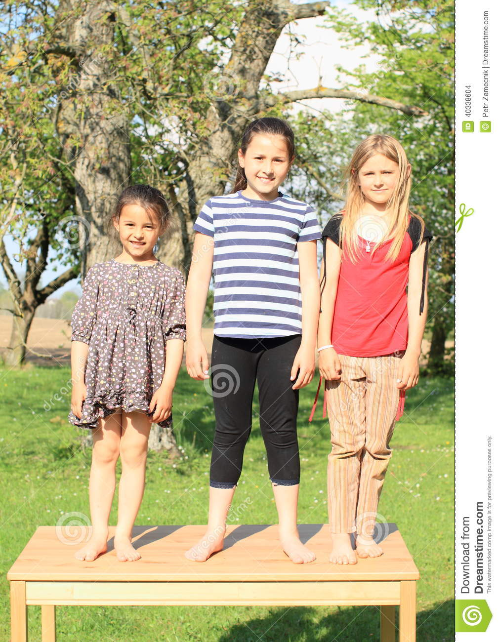 Three Smiling Girls Standing On The Table Stock Photo