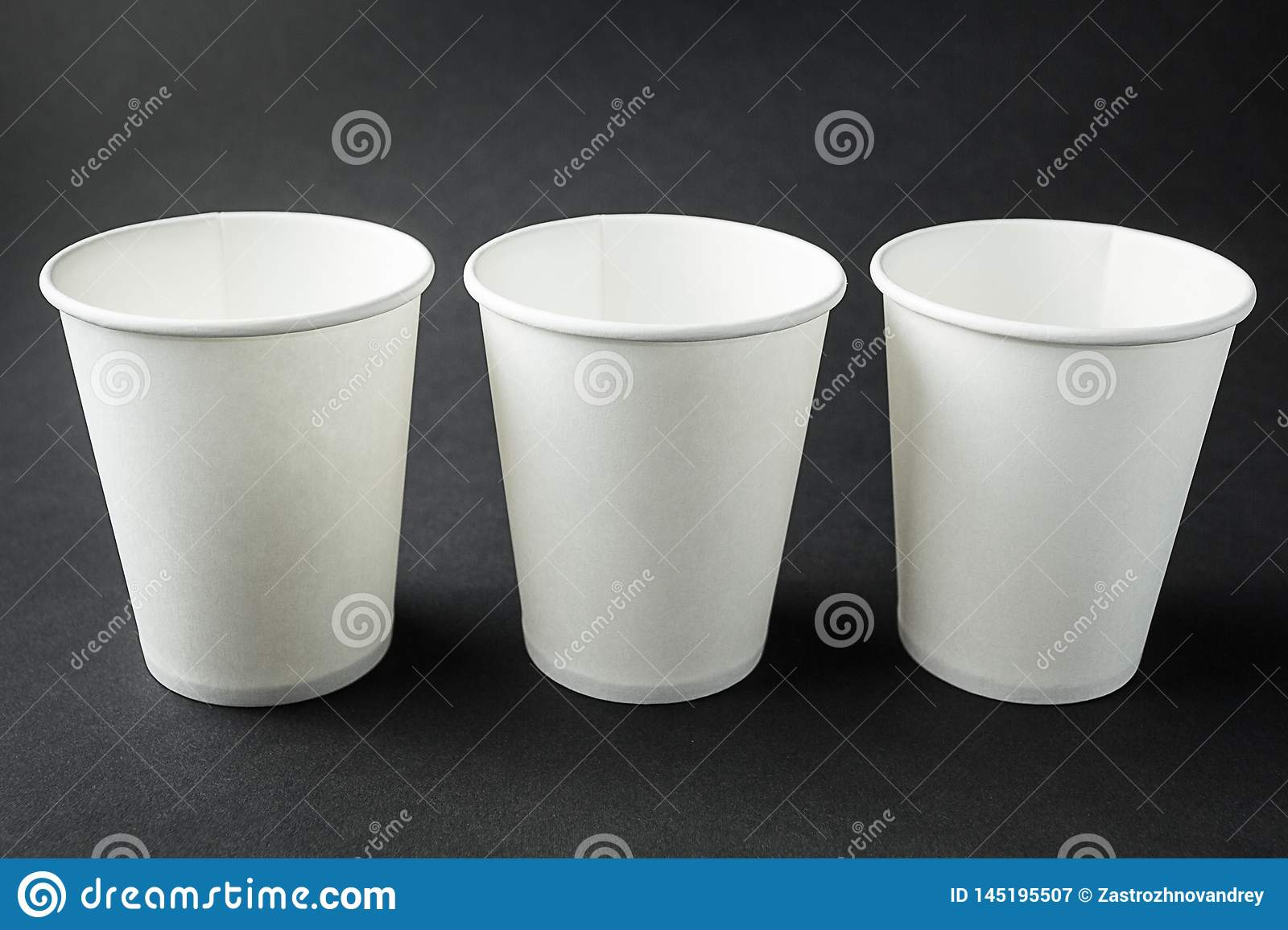 Three take away white paper cups for hot coffee, tea, juice and other beverages isolated on black. Retail mockup presentation
