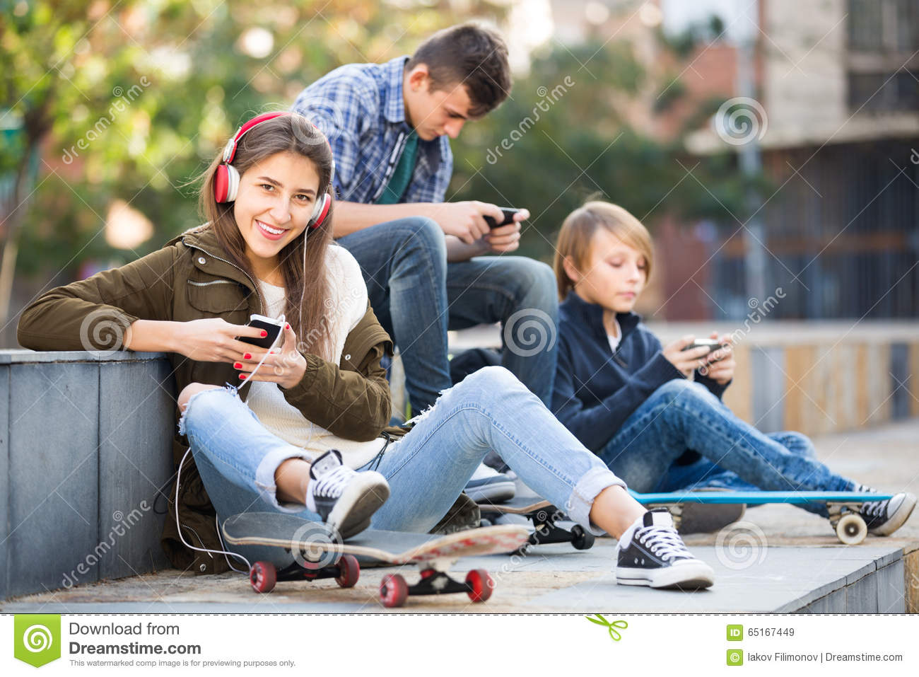 Three teenagers with smartphones