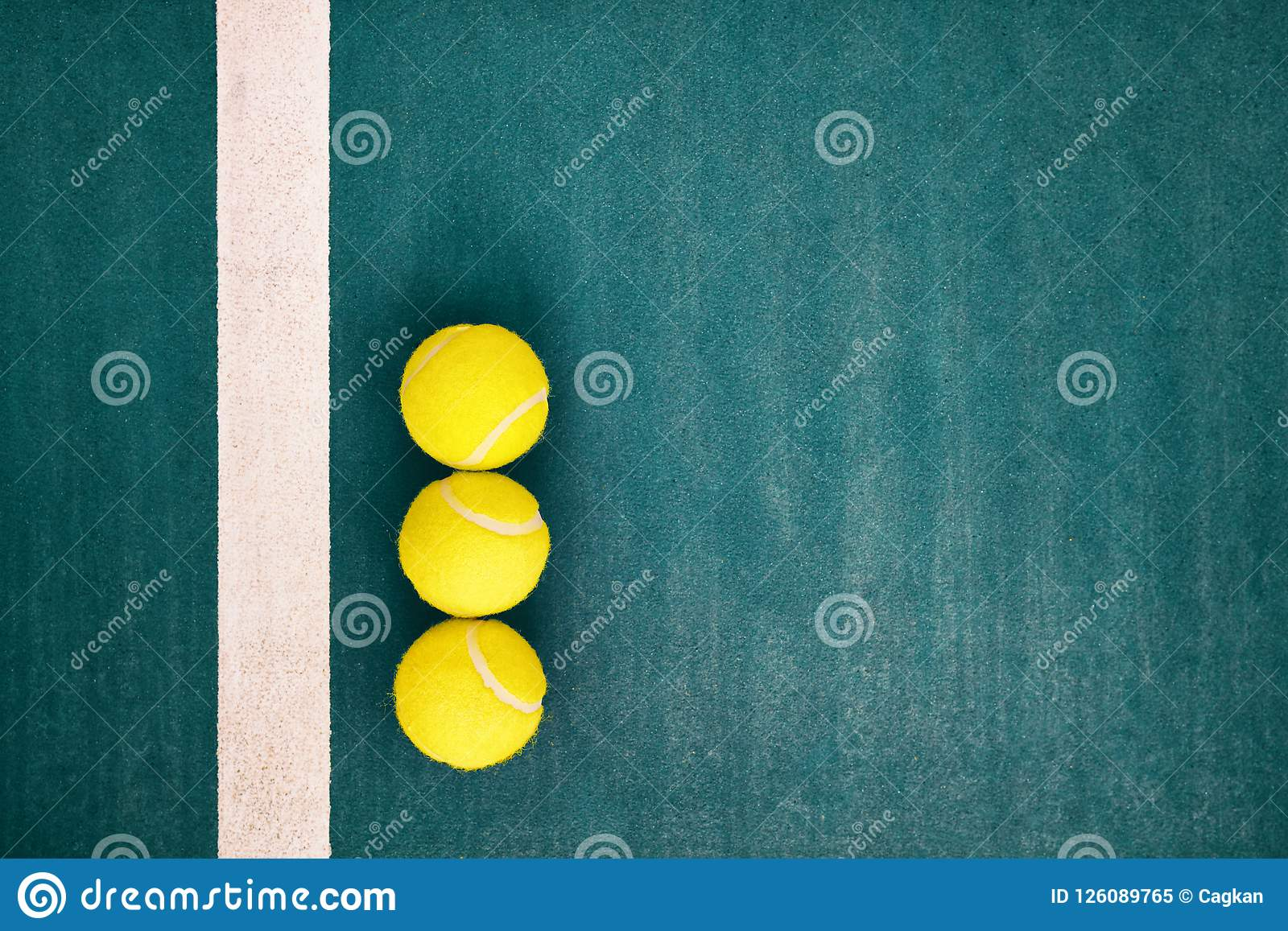 Three Tennis Balls Near The Line Of A Concrete Court Stock Image