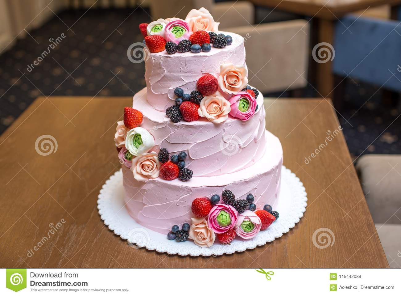Three Tiered Pink Wedding Cake Decorated With Berries And Flowers