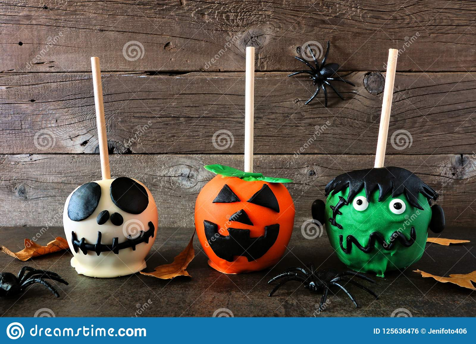three unique halloween candy apples against rustic wood stock photo