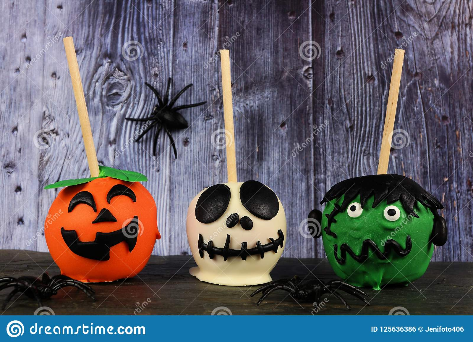 three halloween candy apples against a spooky wood background stock