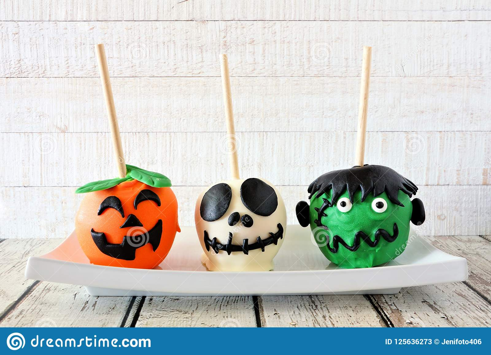three unique halloween candy apples against white wood stock image