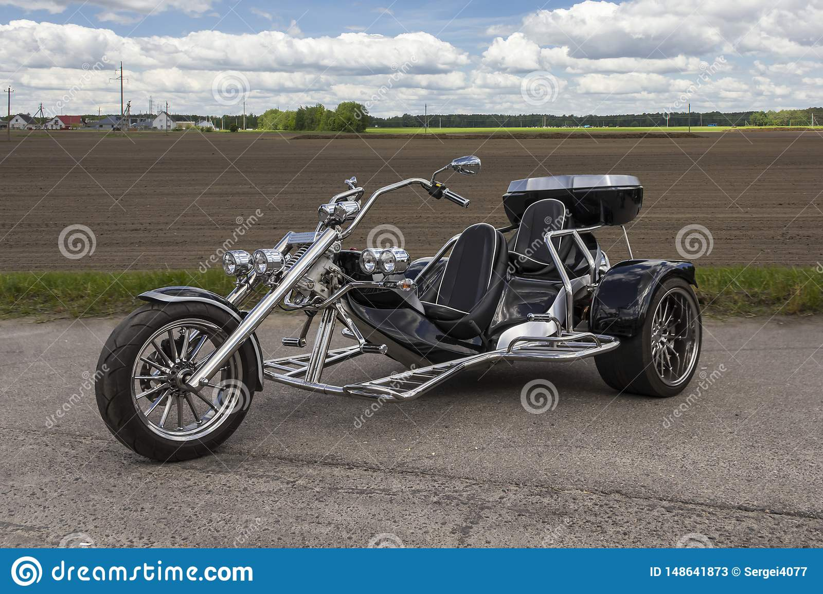 Three-wheeled motorcycle stands in the parking lot near the field