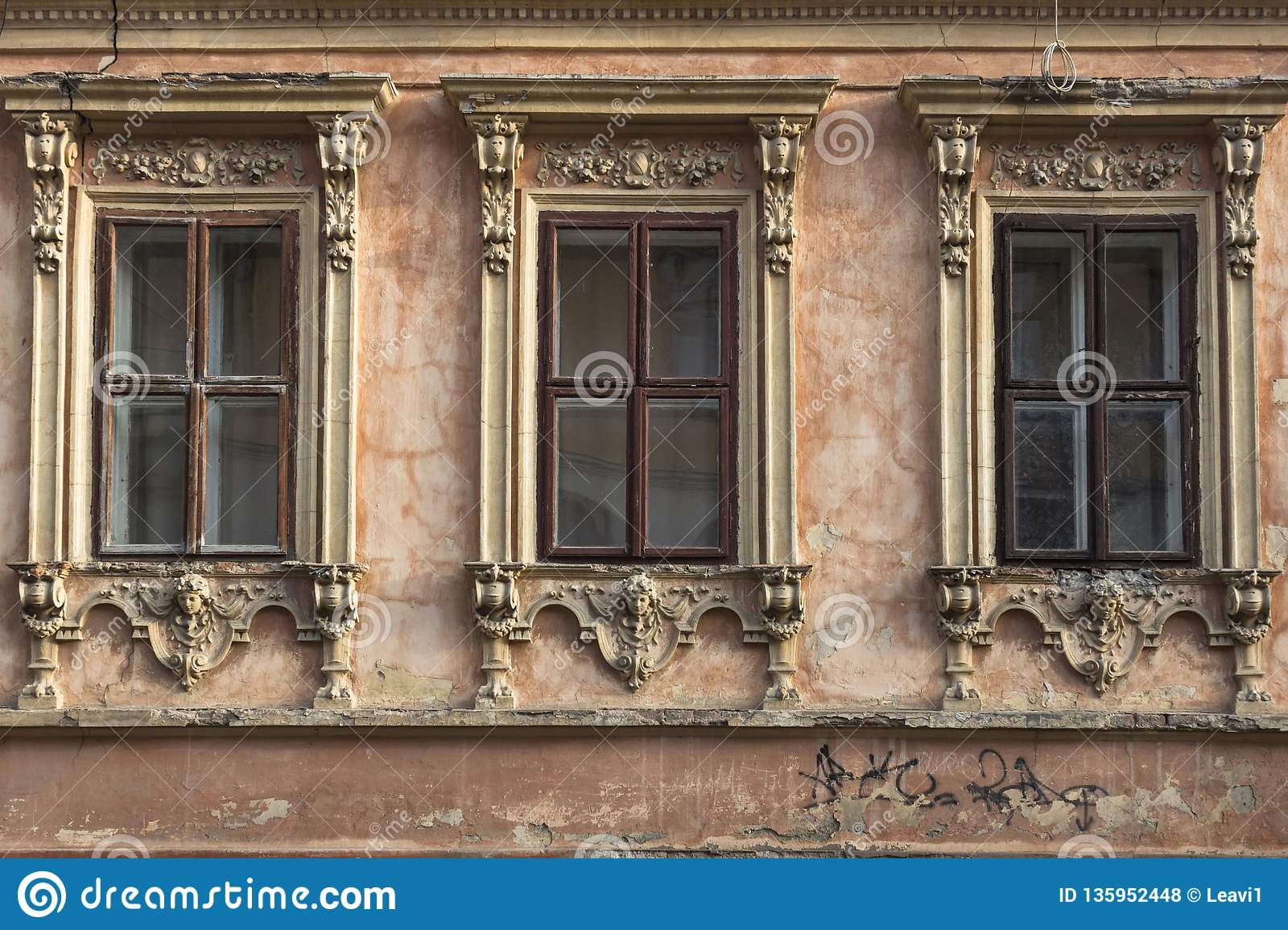 Three windows with carved frames on the facade of the old house