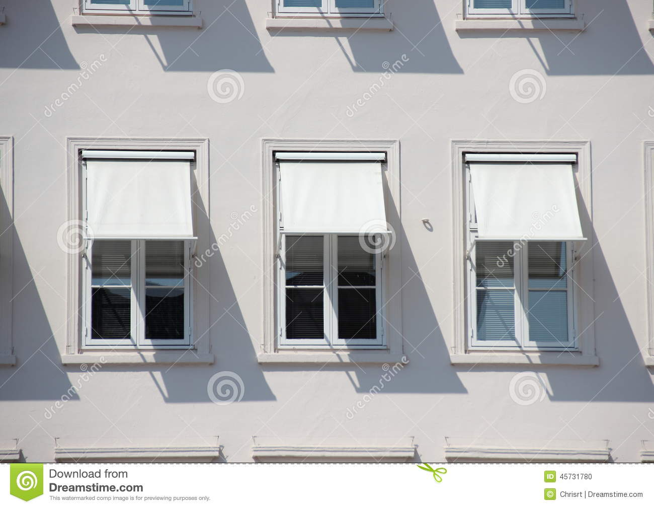 Three Windows On Grey Building With White Awnings And