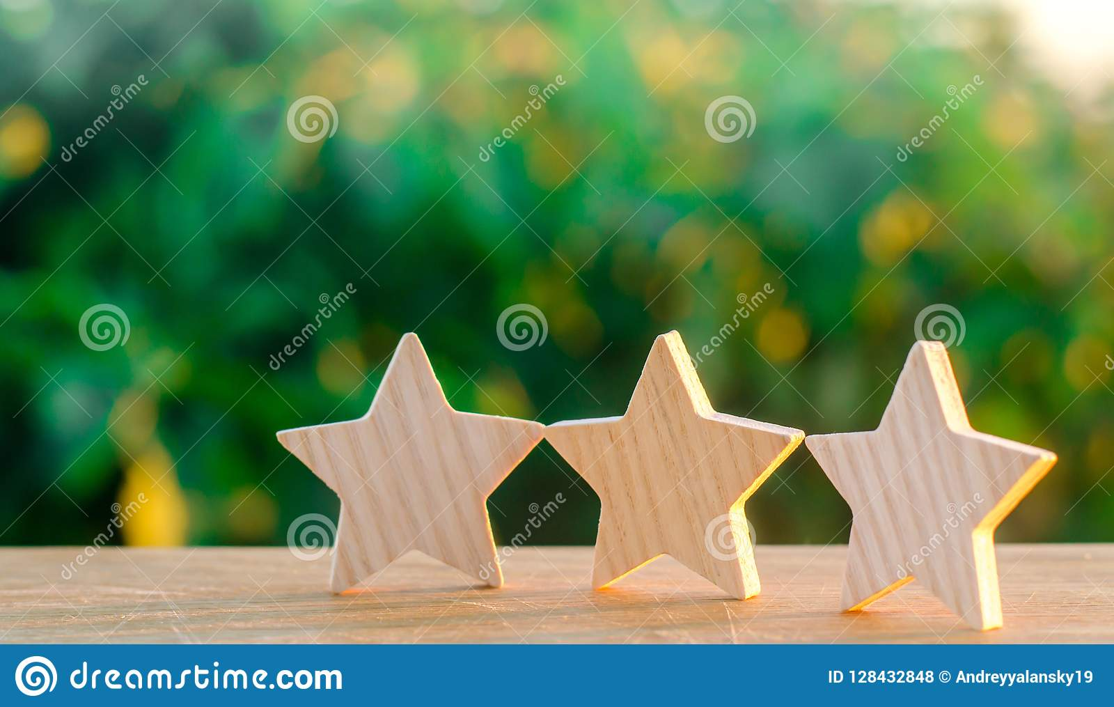 Three wooden stars on a background of green bokeh background. The concept of the rating of hotels and restaurants, the evaluation