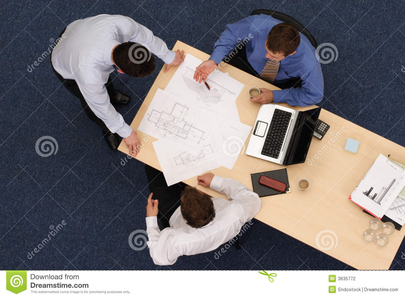 Three working business people over blue prints