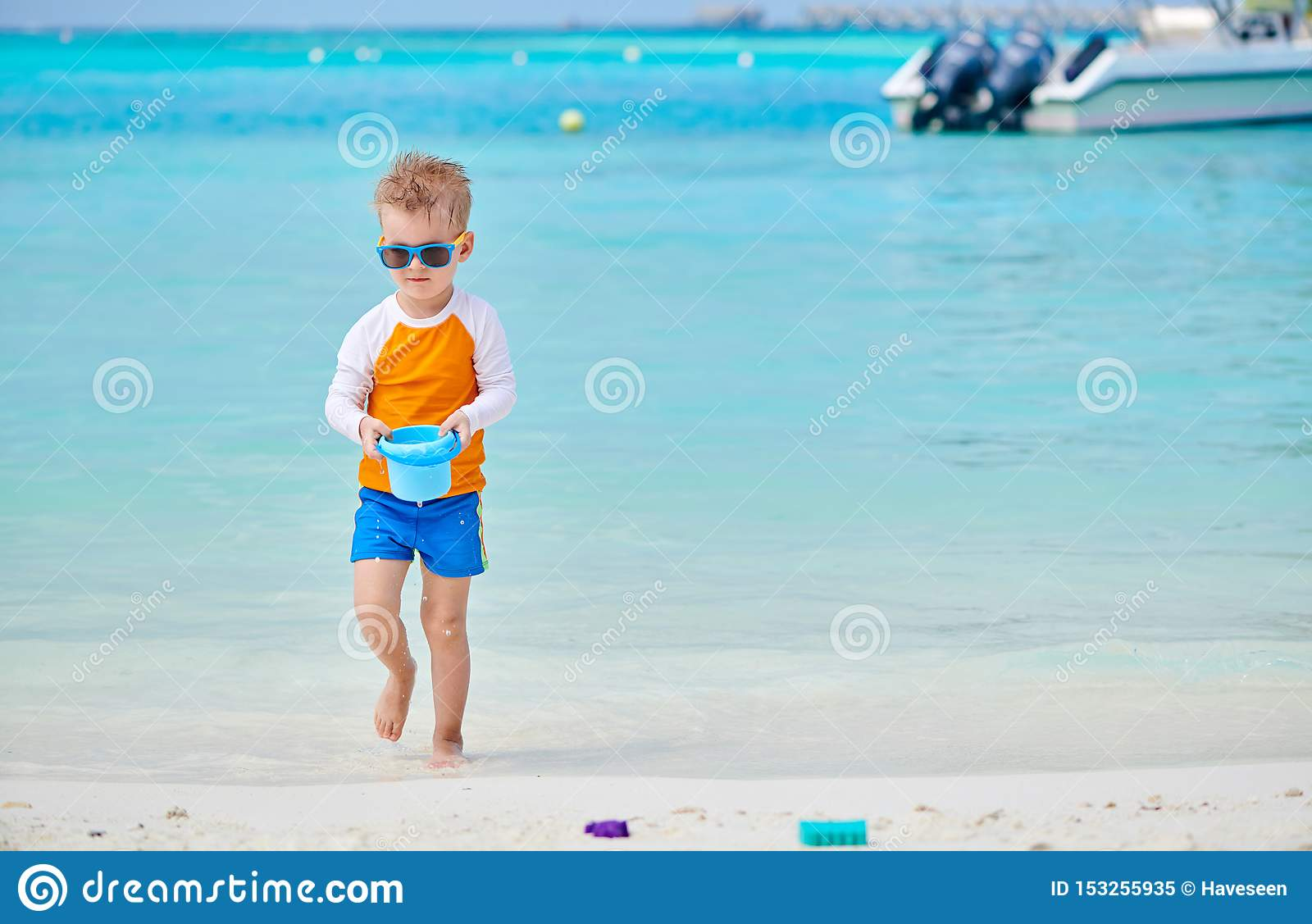 Three year old toddler playing on beach