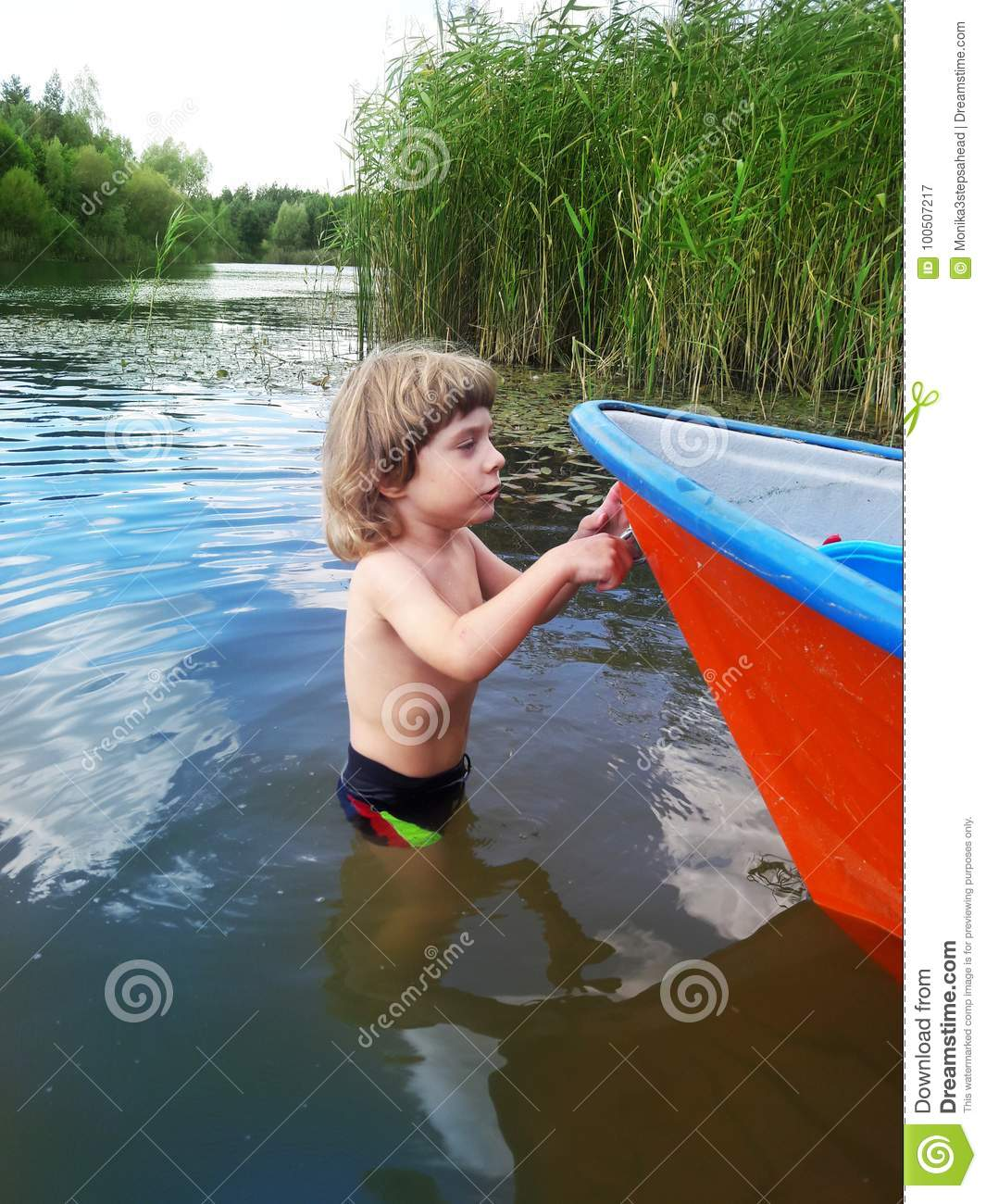 Three years old boy and a boat in a water