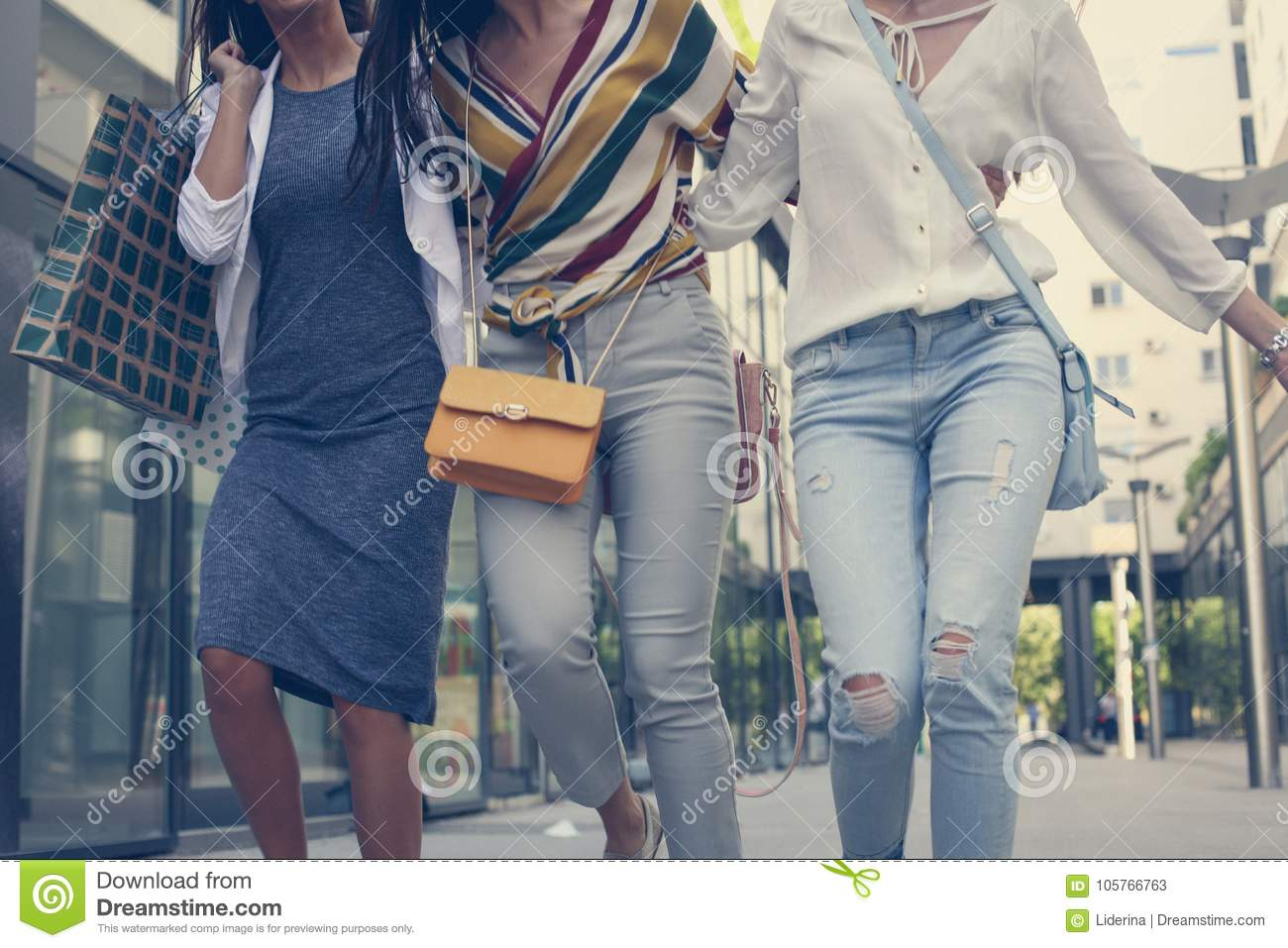 Three young girls walking happy with shopping bags.