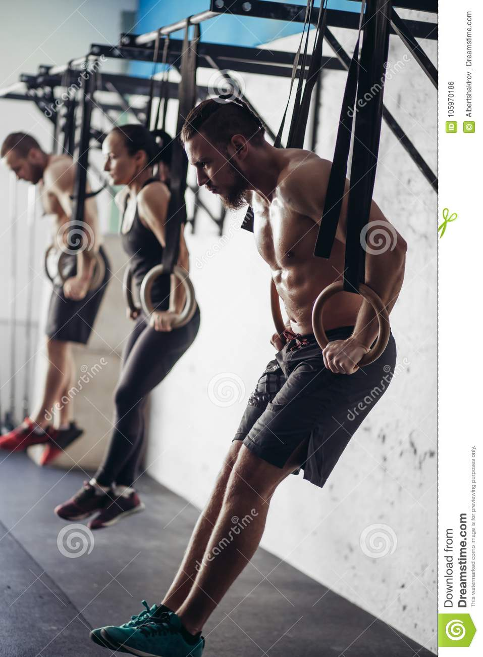 Three Young Male And Female Adults Doing Pull Ups On Rings