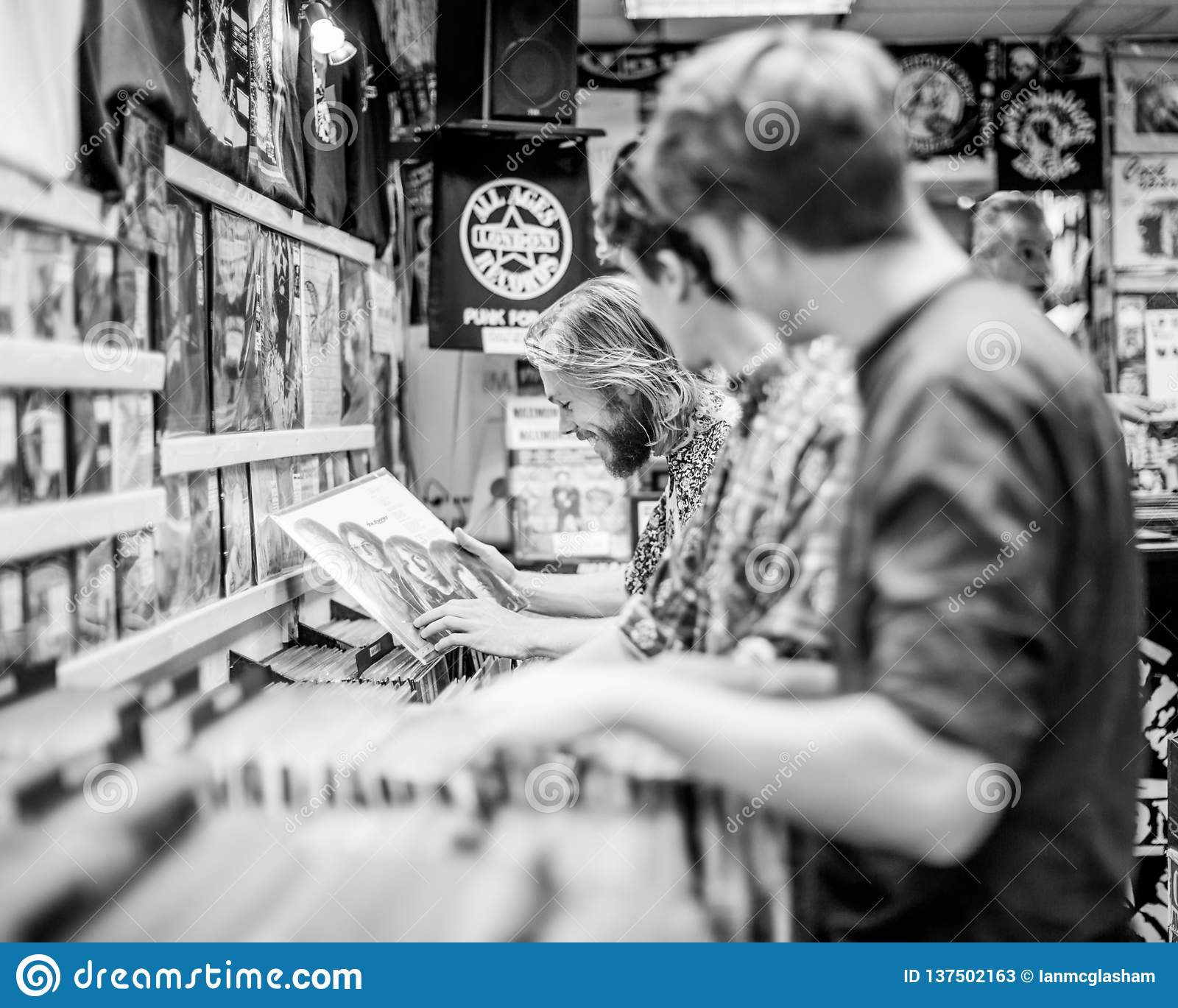 Young men looking at vinyl records in a store or shop.