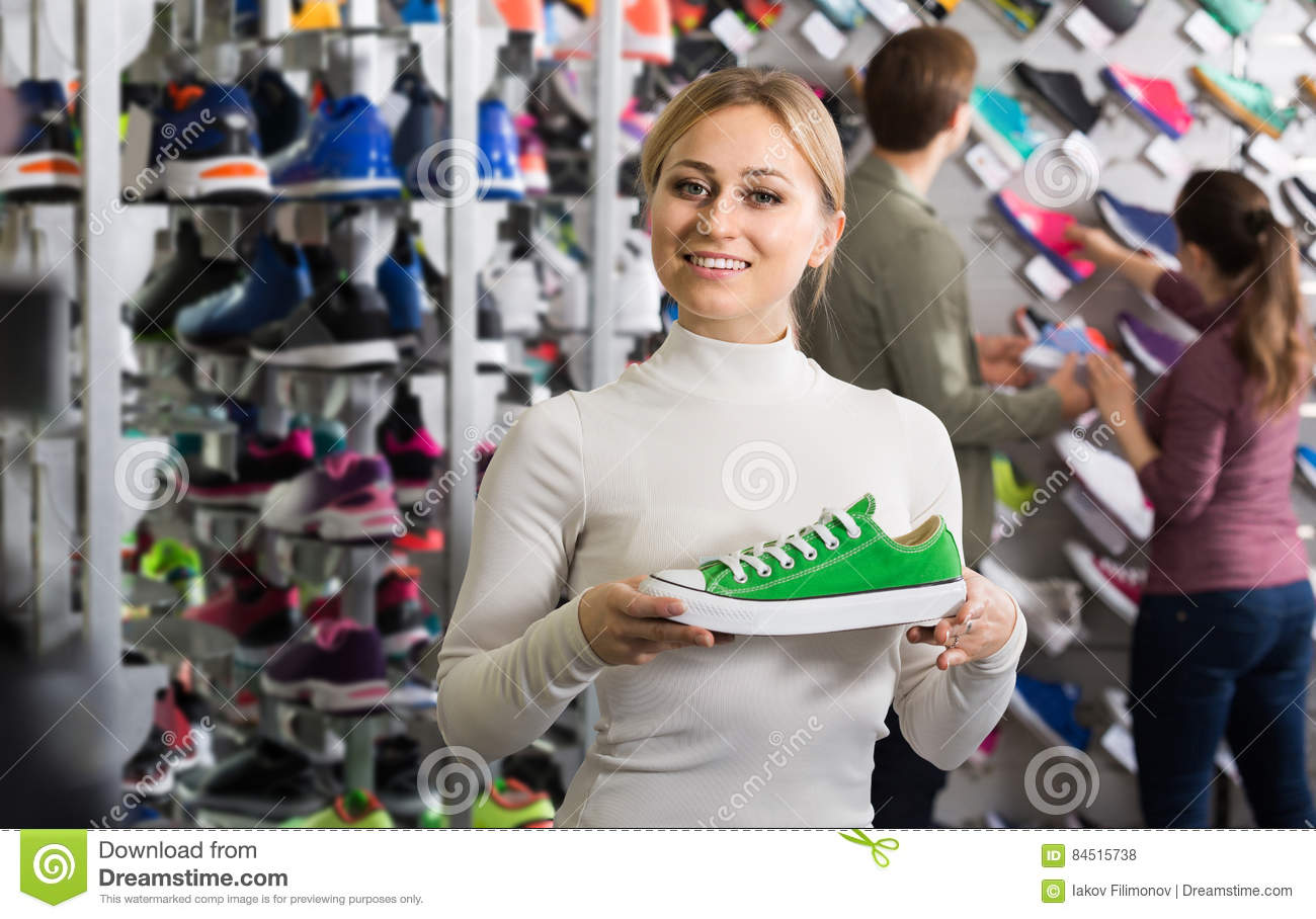 Three young persons showing an assortment of the shoes in the st