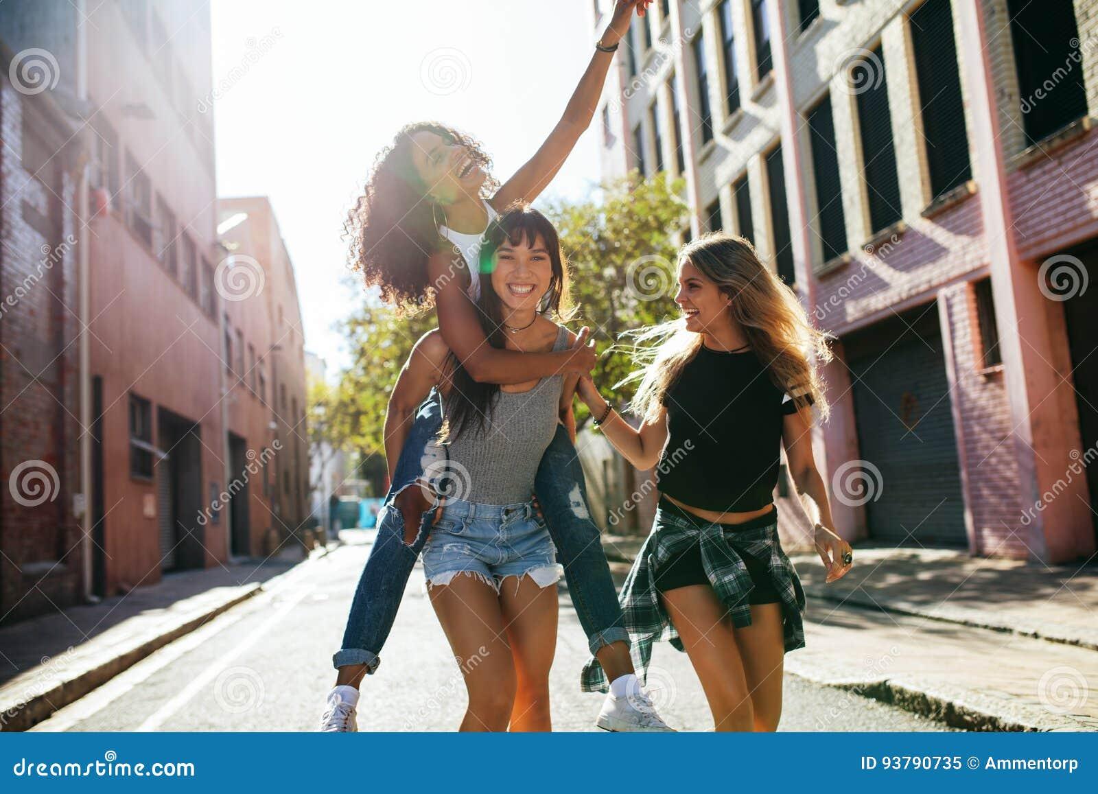 Three young woman having fun on city street