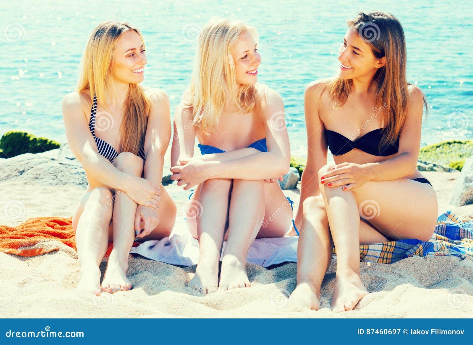 f9407435a0294 Three joyful smiling girls in bikini relaxing on sandy beach on sunny day
