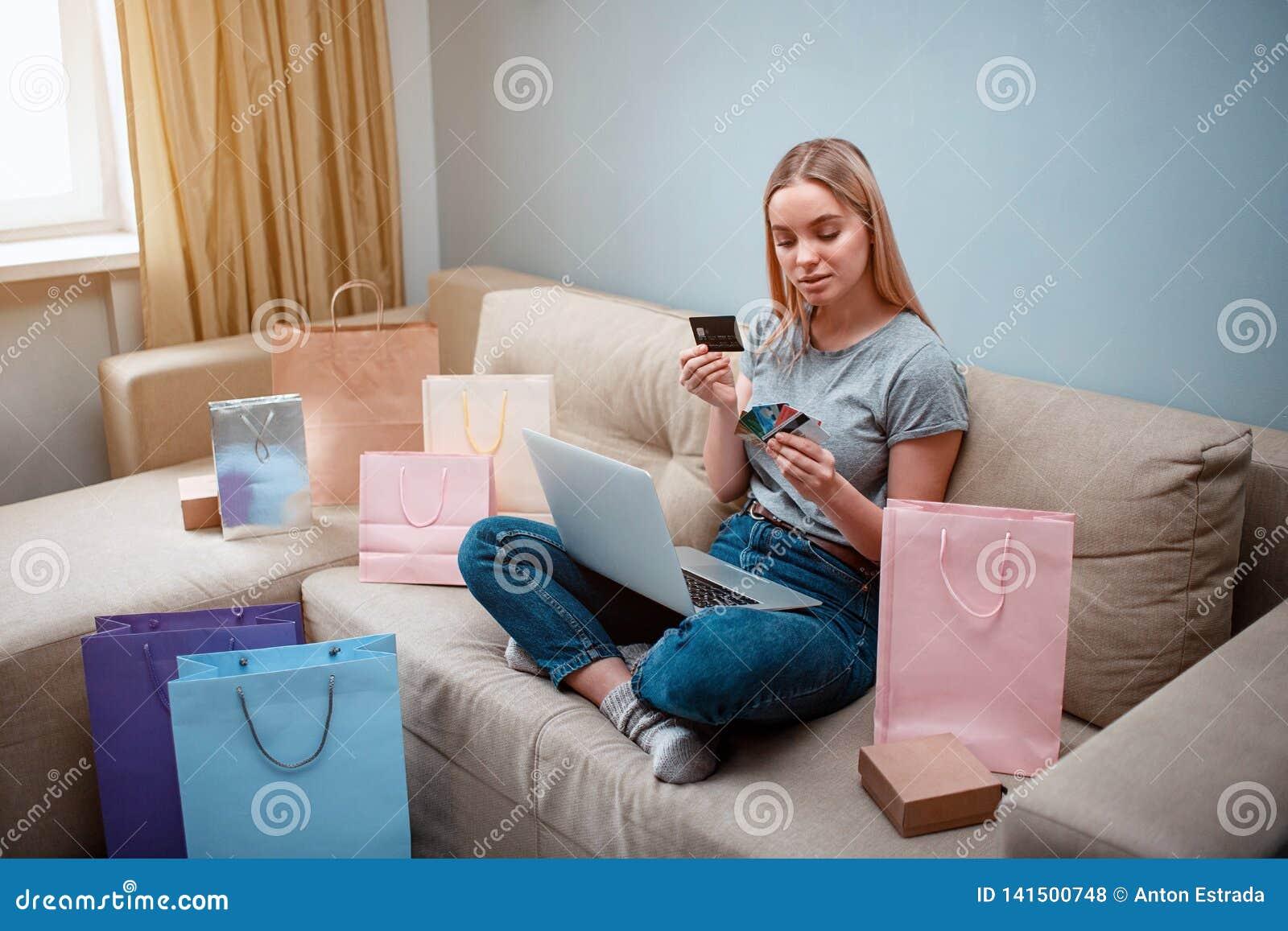 Thuis online winkelend De jonge gelukkige klant met laptop kiest beste creditcard voor betaling in online winkel terwijl