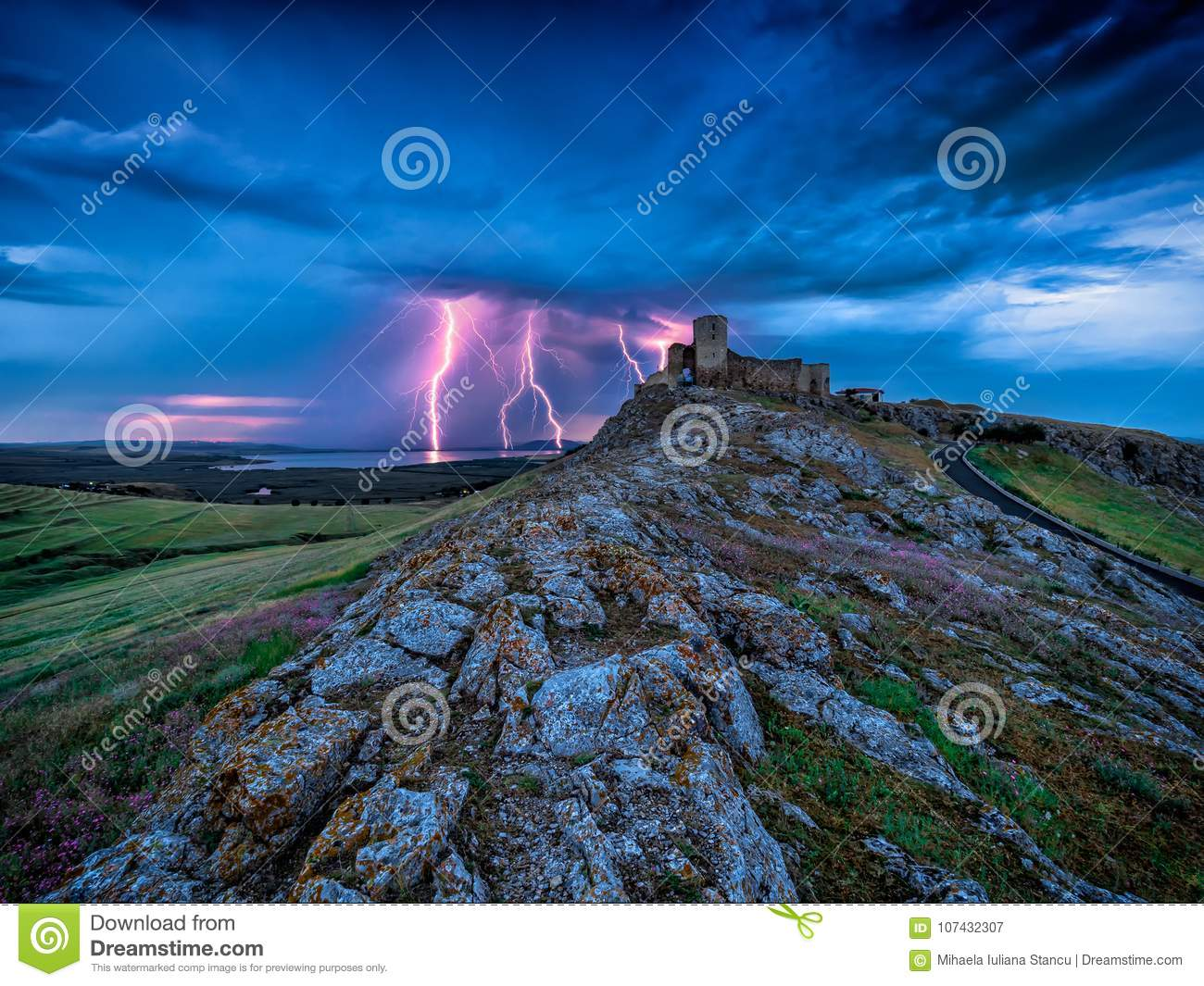 Thunderbolts lightning on a cloudy evening blue sky over old Enisala stronghold citadel