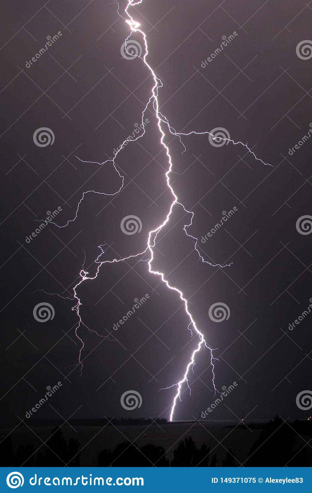 Thunderstorm and lightning strike over the river at night