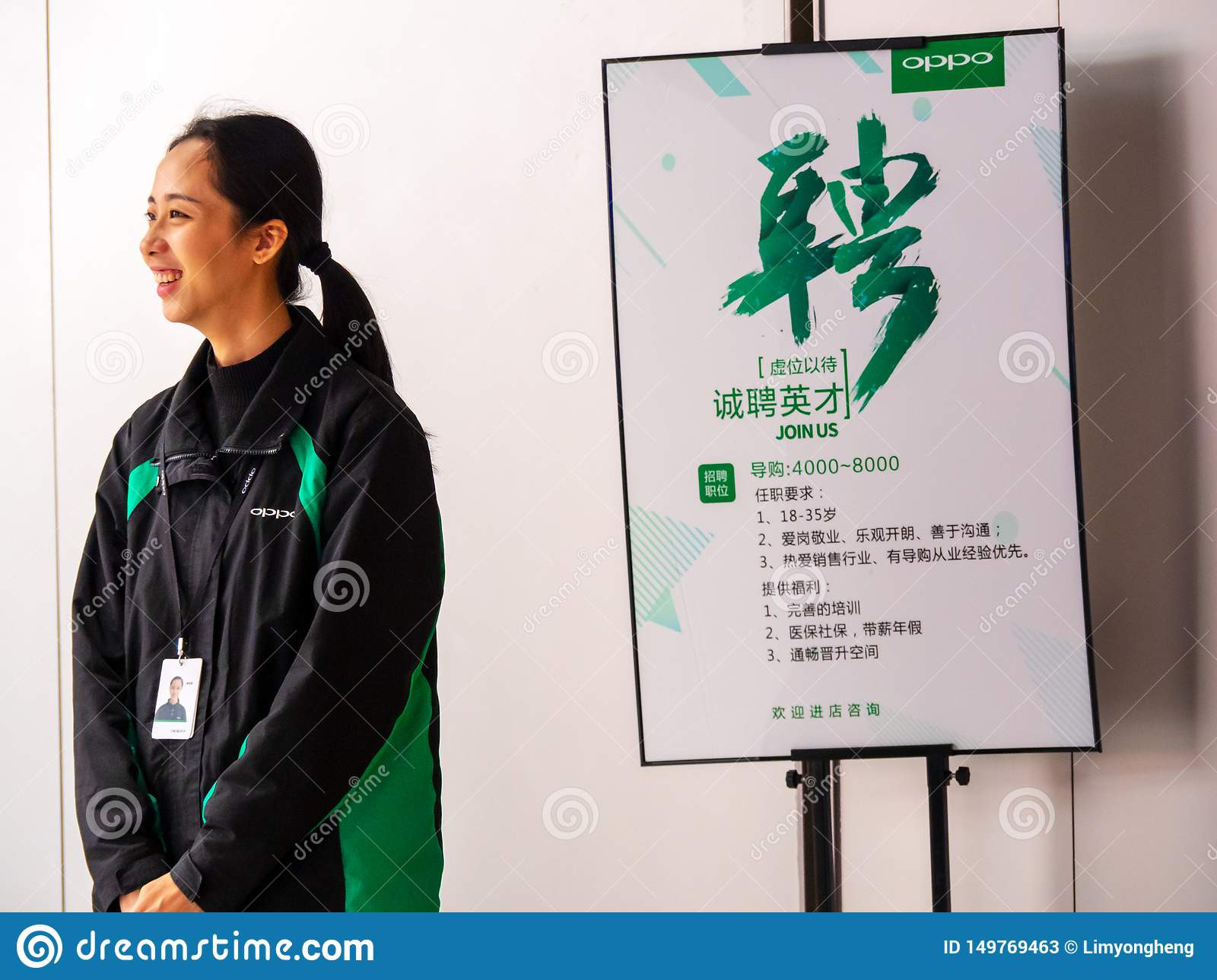 TIANHE, GUANGZHOU CITY, CHINA - 7 MAR 2019 - A smiling Oppo employee stands next to an staff recruitment poster seeking sales