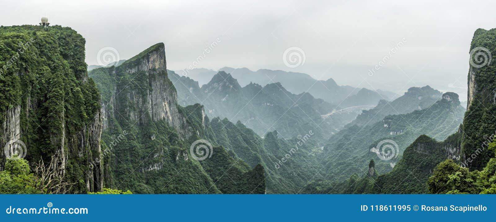 Tianmen berg som är bekant som porten för himmel` som s omges av den gröna skogen och misten på Zhangjiagie, Hunan landskap, Kina