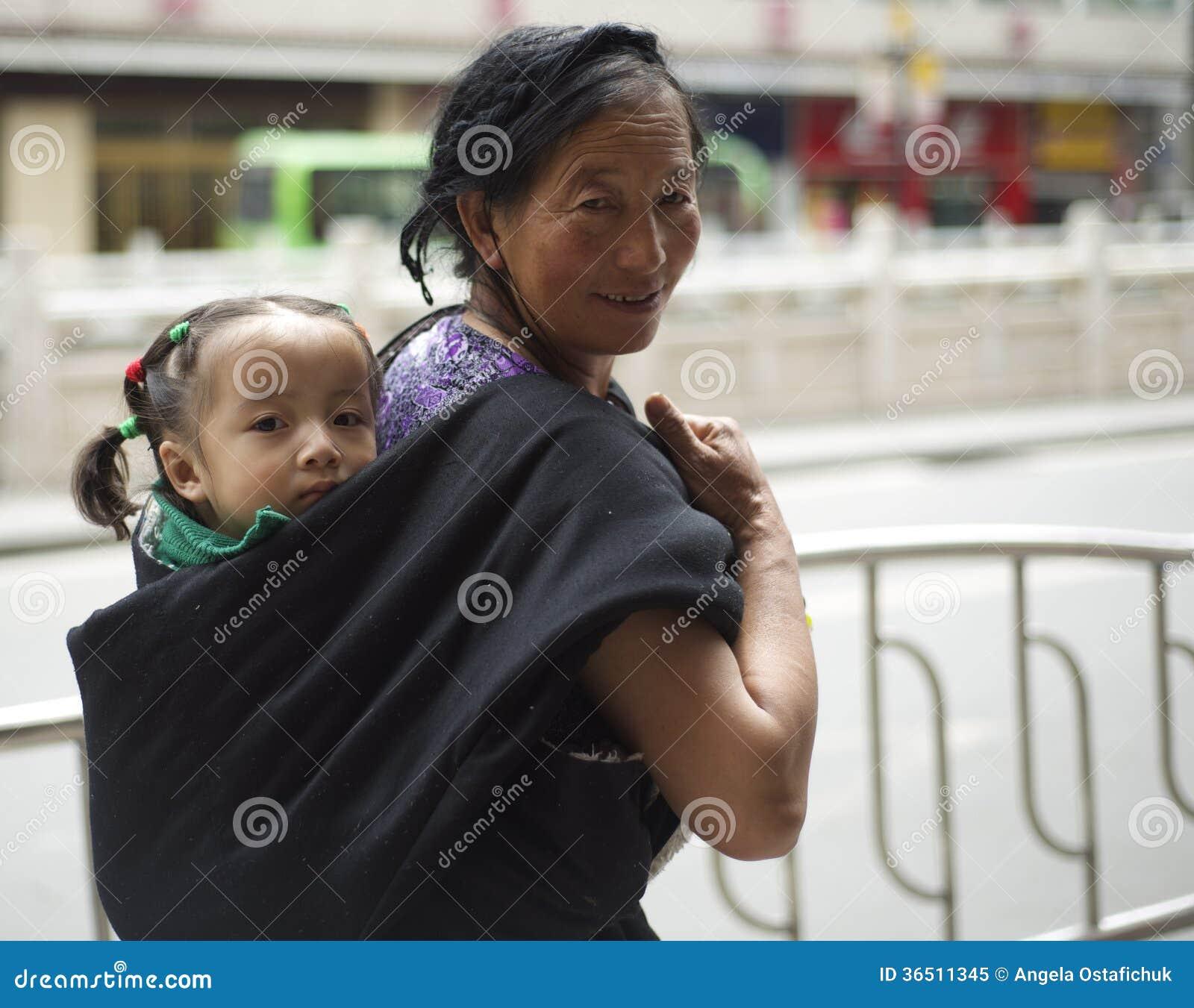 Tibetan kvinna med barnet